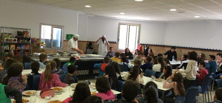 Un pizzero profesional cocina en directo pizzas artesanales en el comedor escolar